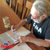 Willie Nelson, Farm Aid President, signs 2019 grant checks.